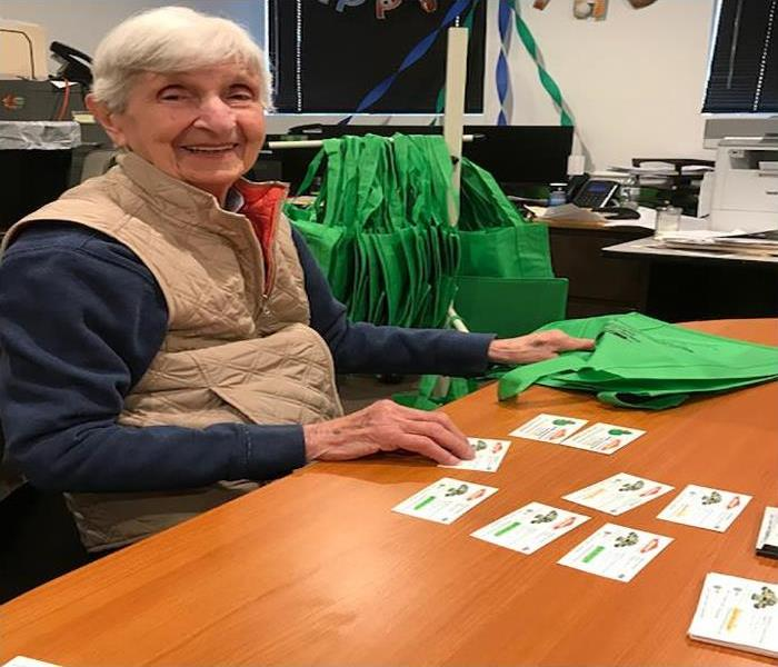 A woman sitting at a desk with SERVPRO cards and green bags