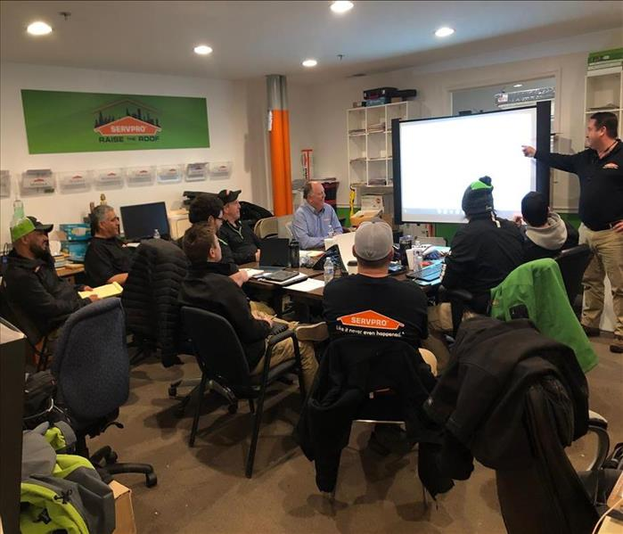 A group of people sitting in a room looking at a projector for SERVPRO
