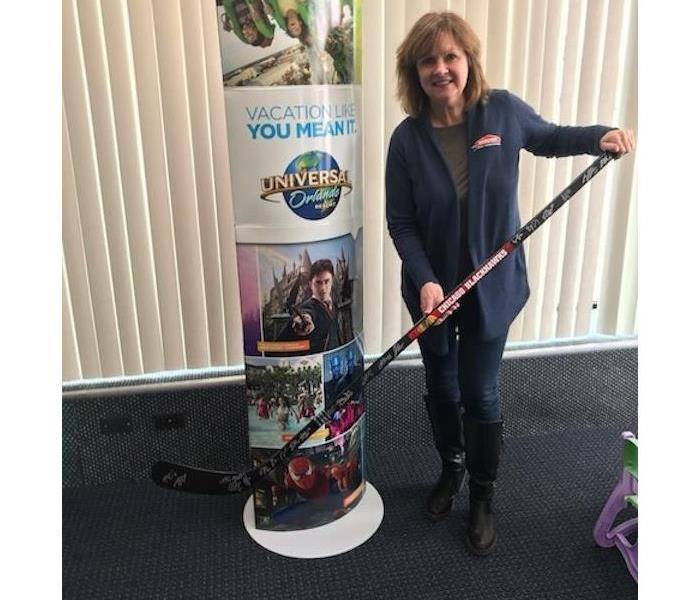 A woman holding a hockey stick in a room with grey carpeting