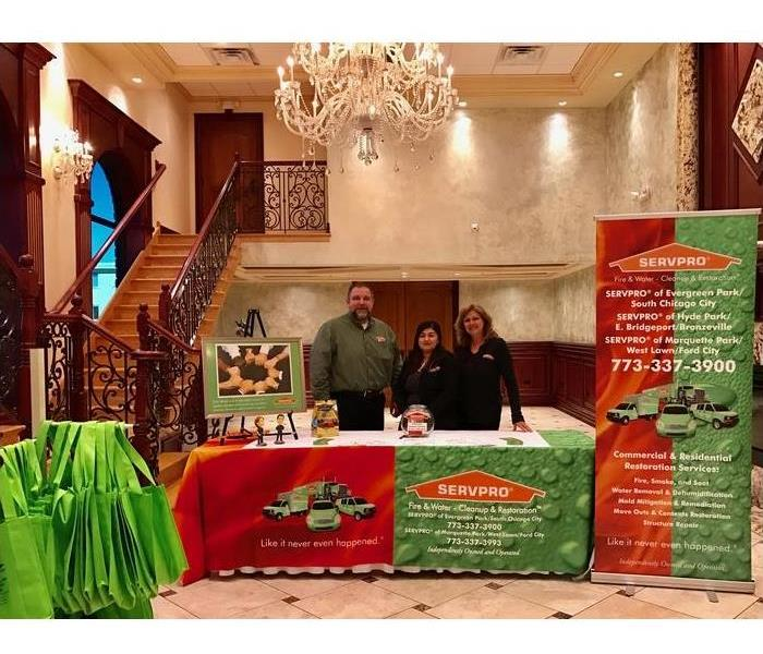 Three SERVPRO employees standing with SERVPRO banners