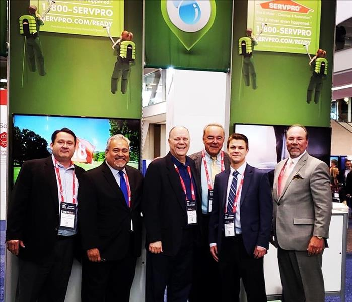 A group of men standing in front of SERVPRO banners