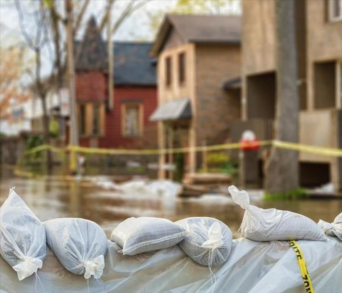 Standing water and bags of sand in front of a home.