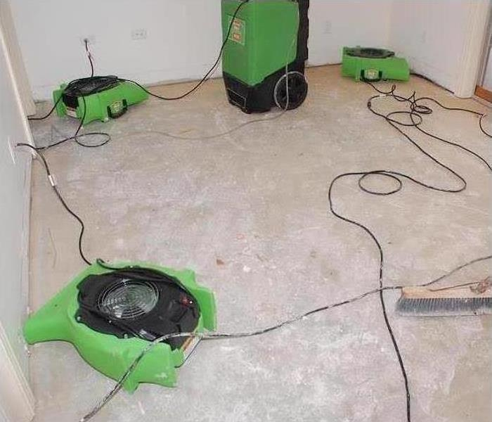 Our commercial air movers and dehumidifiers working to dry the sub-flooring in this home