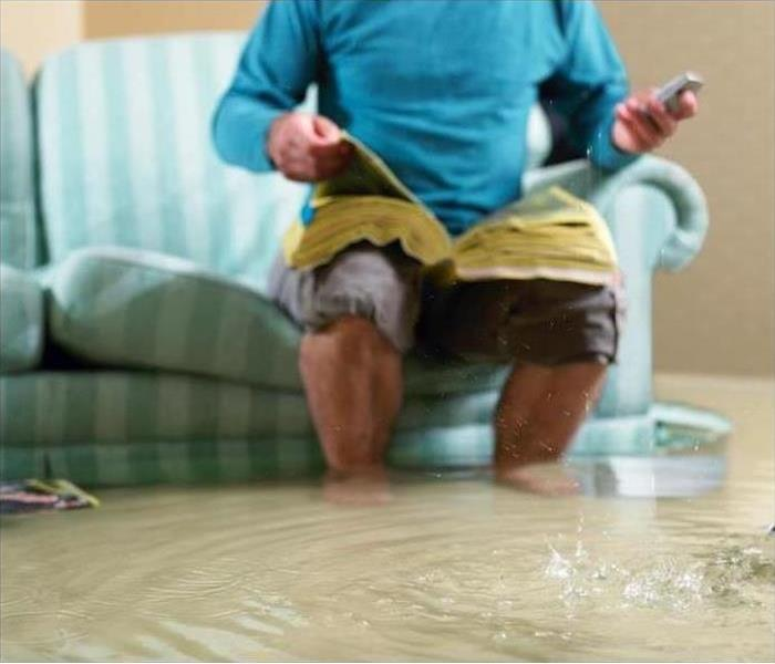 Man sitting on sofa as water rises in living room