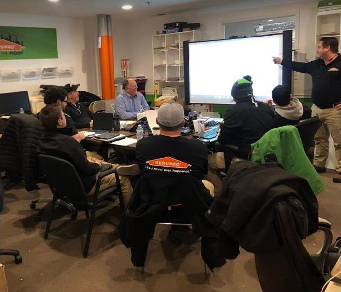 SERVPRO technicians sitting around table during continuing education